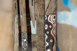 Close-up of wooden poles decorated with Aboriginal motifs