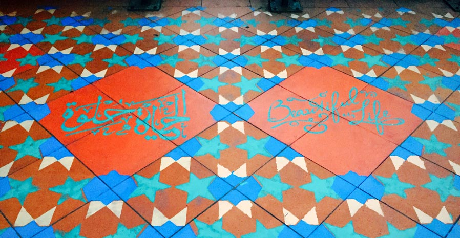 Coloured floor tiles with Arabic star patterns and script