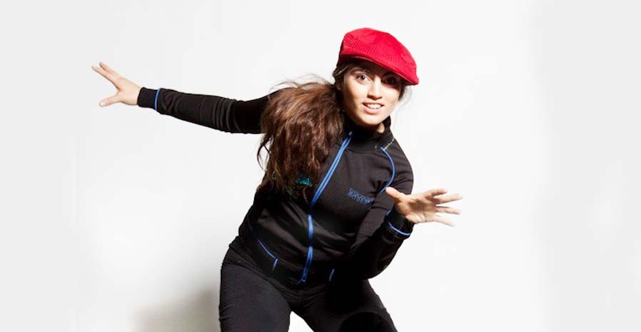 Young women wearing a black tracksuit and red hat, dancing