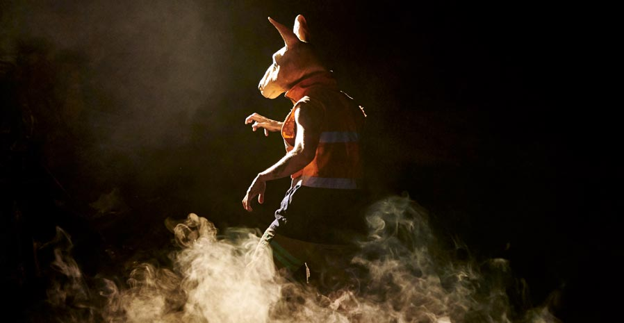 Performer on a smoky stage, wearing a kangaroo mask