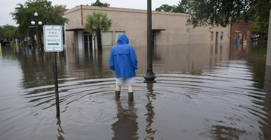 Person wearing a raincoat standing shin-deep in floodwaters of an inner-city street