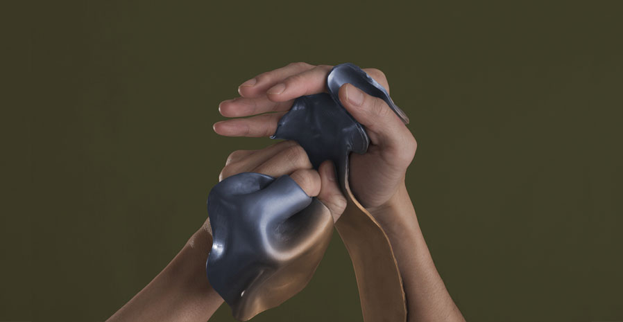 A pair of hands partially covered in moulded pieces of plastic.