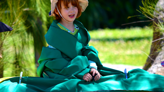 Girl in hat sitting on grass wrapped in green cloth