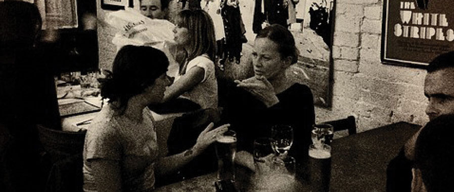 Black and white photo people talking in a pub