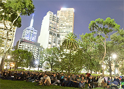A crowd of people sitting in a park at night with the city skyline behind them.