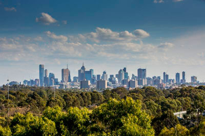 Distant view of Melbourne CBD buildings, trees in the foreground