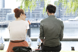 Male and female couple sitting on a wall in the city