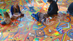 Children and adults sitting on a wooden floor with coloured line drawings on it.