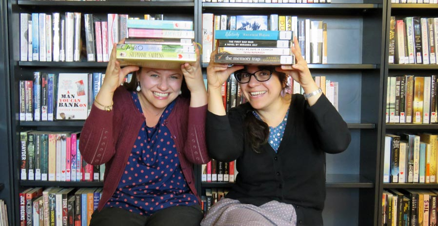 Two women in front of library shelves, each holding a stack of paperbaks above their faces