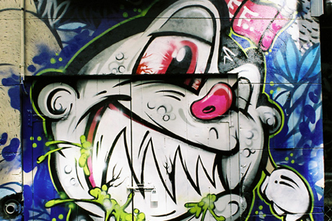 Street art of a cartoon smiling face with pointy teeth