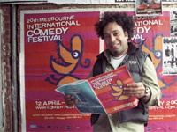 Indigenous person standing in front of a Melbourne Comedy Festival poster