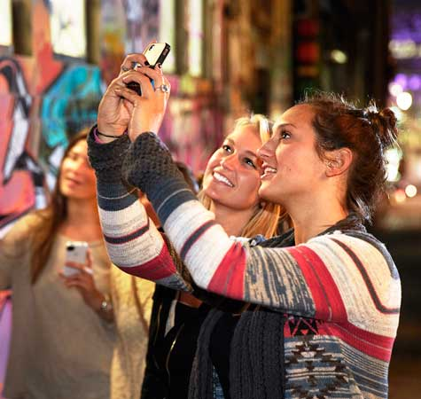 Two woman taking self portrait with ohone in laneway