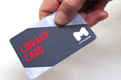 A hand holding a gray and blue City of Melbourne library card.