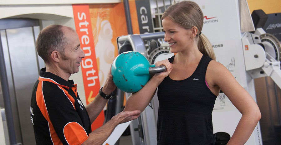Woman working with a personal trainer and using weights