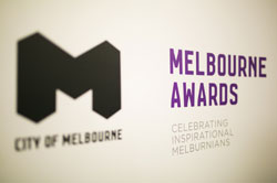 Angled photo of sign that reads 'City of Melbourne' - 'Melbourne Awards' - 'Celebrating inspirational Melburnians'