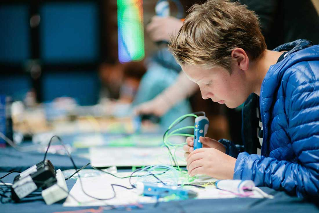 A boy using electronics tools and equipment
