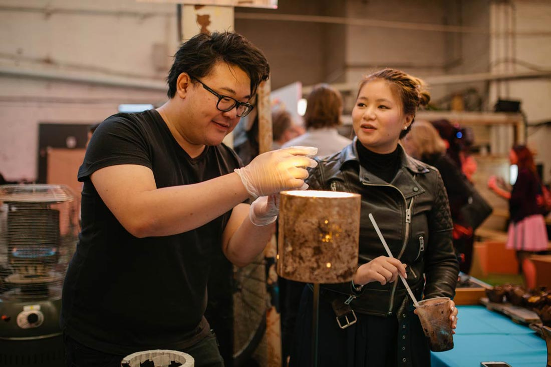 Two people adjusting a lamp-like object at the exhibition
