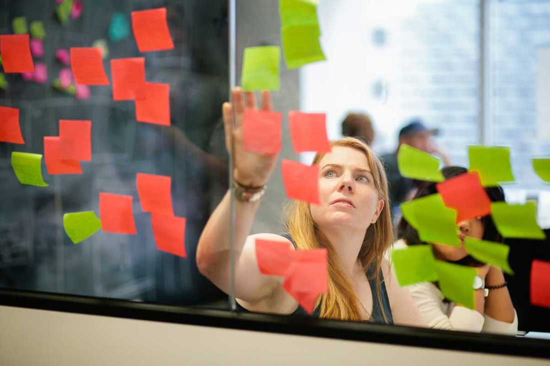 A woman reading coloured post-it notes attached to a window