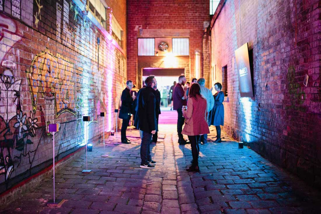 A group of people looking at exhibits in a cobbled laneway at night