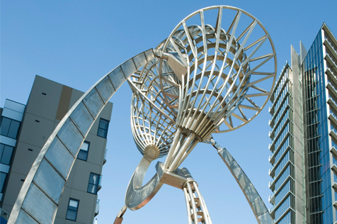 Stainless-steel sculpture among city buildings