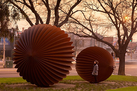 Ribbed spherical metal seed-like sculptures in park