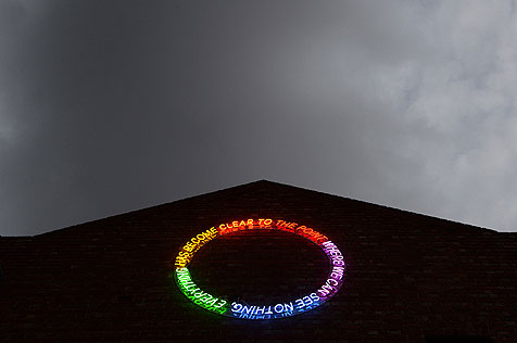 Circular neon sign on gabled building, in spectrum of green, yellow, orange, red, purple and blue spelling out the words 'to the point where we can see nothing everything has become clear'