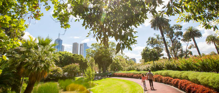 Two people walking through a park near the city