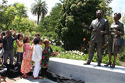 A group of people standing in front of the Pastor Sir Doug and Lady Gladys Nicholls Memorial.