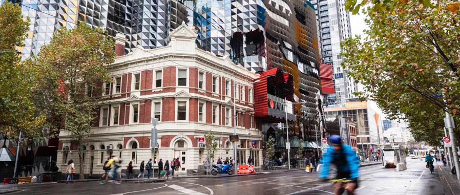 Melbourne city streetscape with RMIT building, cyclists and pedestrians