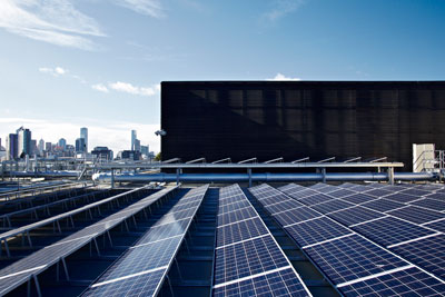 Rows of solar panels on a flat rooftop, Melbourne CBD in the background