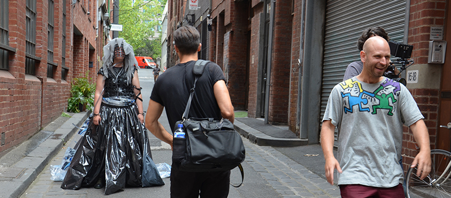 Person in black plastic being filmed in alley