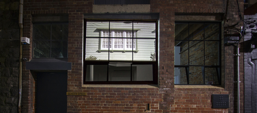 Factory wall with house reflected in windows